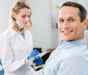 Image of patient sitting on the dentist chair & dentist near the patient