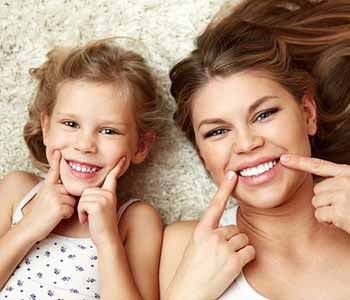 Image of Mother & Daughter showing their teeth with a nice smile